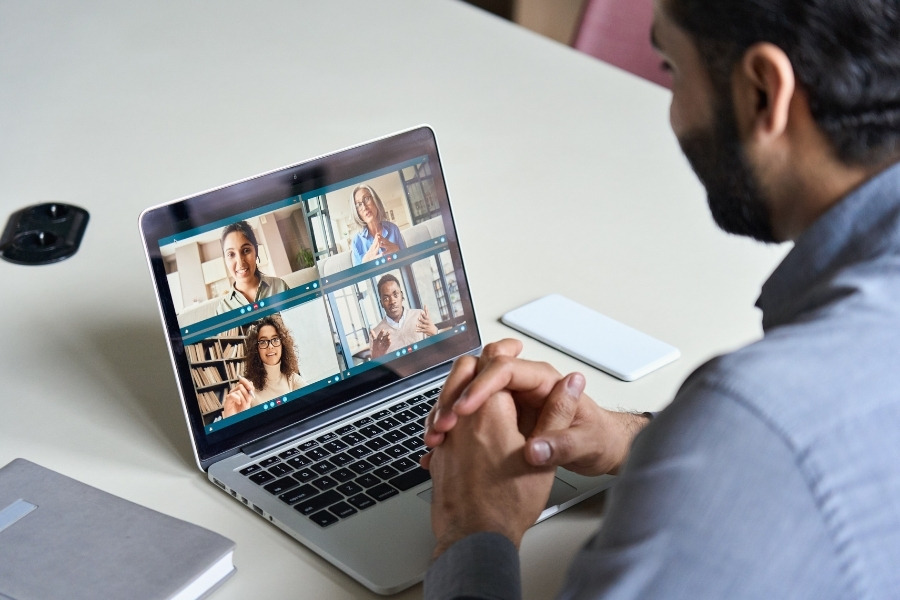 Indian business man having virtual team meeting on video conference call using laptop work from home office talking to diverse people group in remote teamwork online distance chat. Over shoulder view